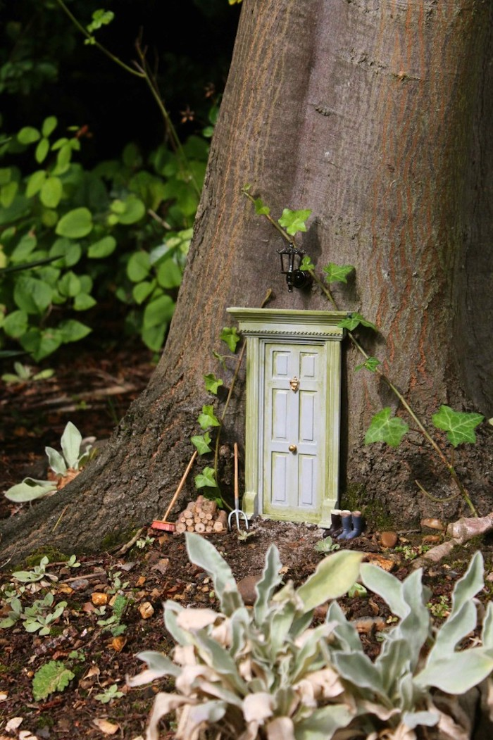 door in vintage style, made in miniature size, with golden knocker and door knob, attached to the trunk of a tree, near two pairs of tiny rain boots, and gardening gear