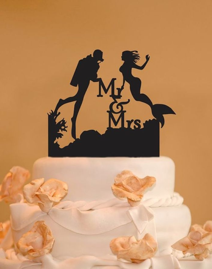 black cake topper, depicting the silhouettes of a mermaid and a diver, along with the words M & Mrs, placed on a white cake with peach-colored fondant flowers