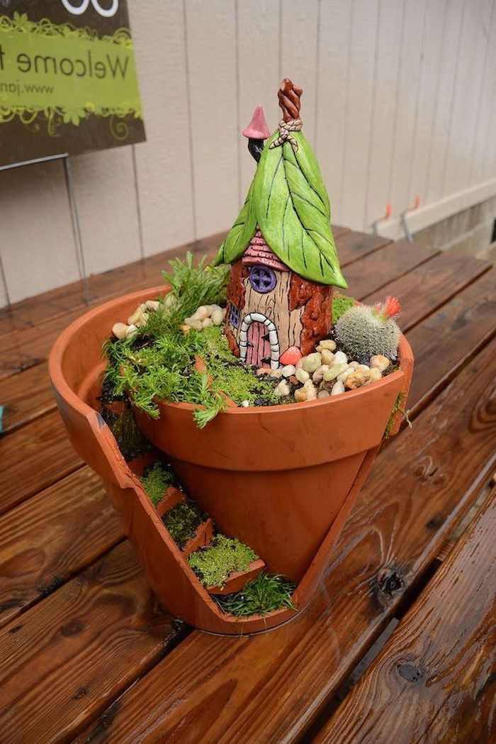 broken pot transformed into a diy fairy house, decorated with faux stairs, green moss and pebbles, cactus and a hand-painted ceramic house figurine