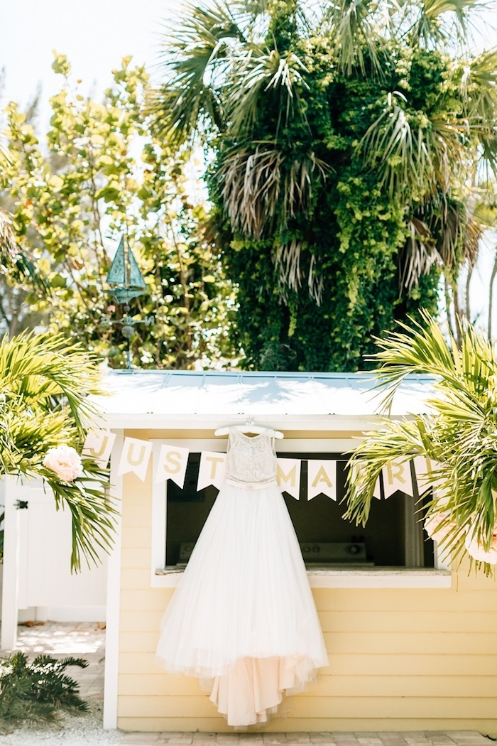 palms and other trees, near a small yellow, wooden beach hut, with a wedding gown hung on the roof, beach weddings in florida