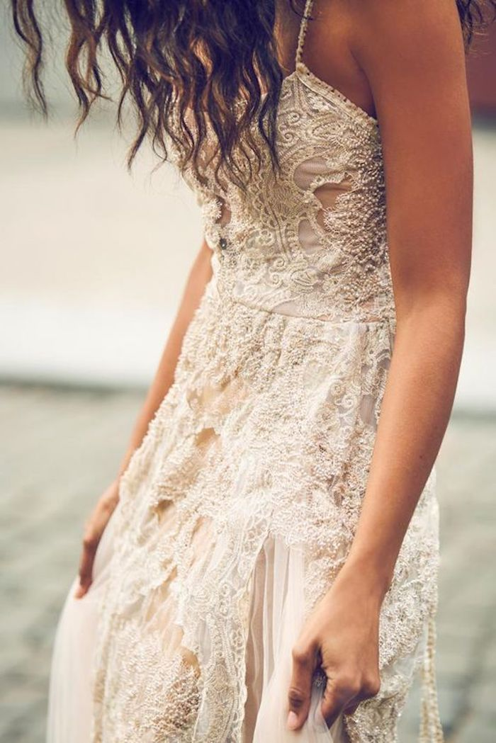 close up of a white and cream-colored, boho lace beach wedding dress, worn by tanned model, with curly brunette hair
