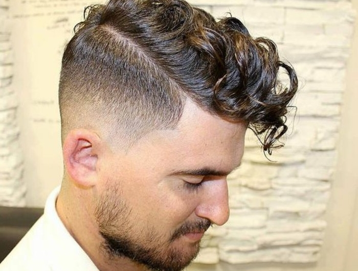 undercut with curly hair, on brunette man in profile, with short beard and mustache, wearing white shirt, curly hairstyles,