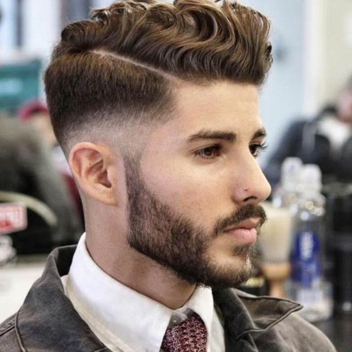 haircuts for curly hair, faded undercut with deep side part, curls swept to one side, trimmed beard and a mustache, white shirt with patterned tie