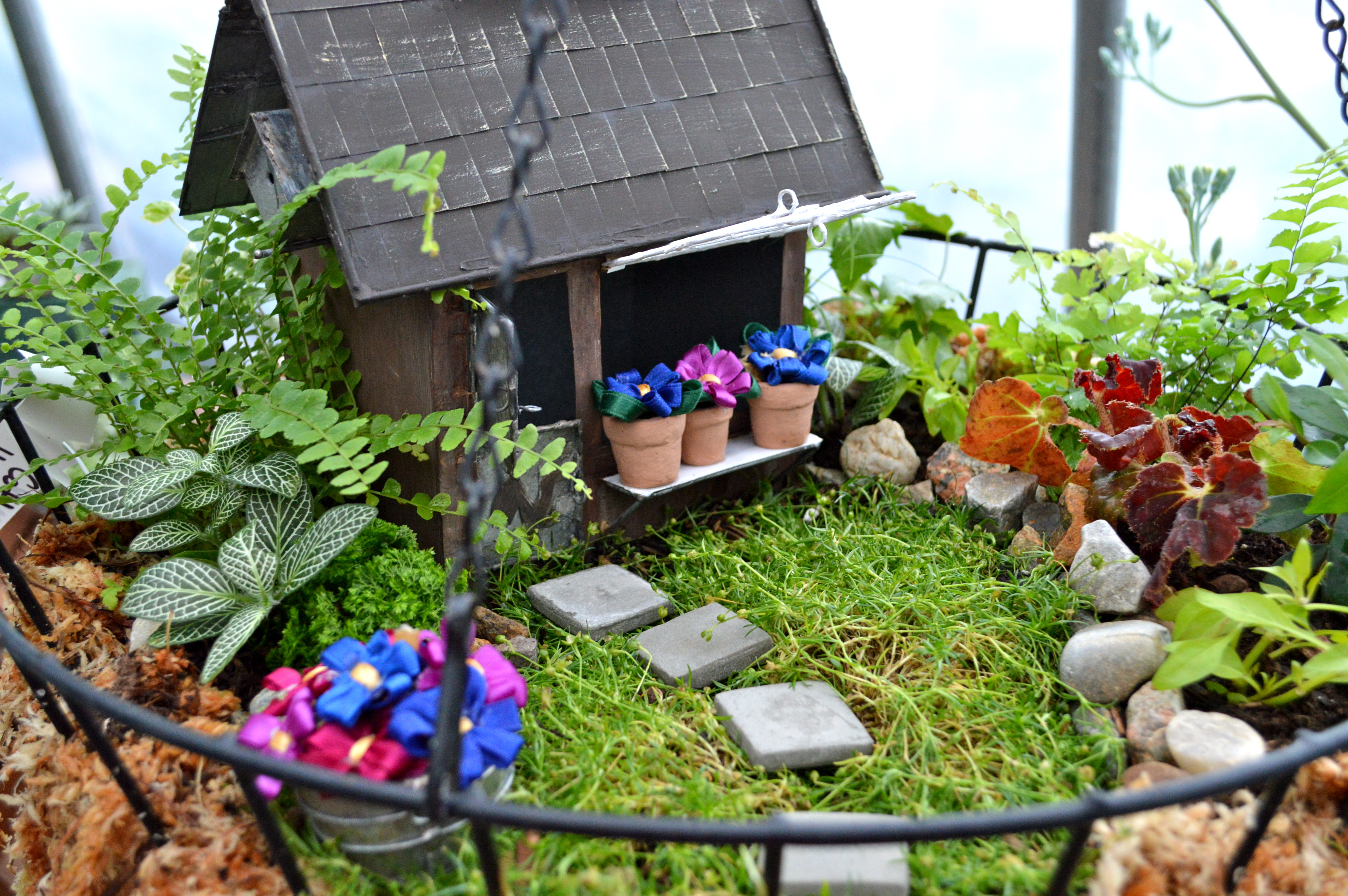 diy fairy house, little wooden house decoration, inside a tiny garden, with small plants, grass and small tiles, model pots with artificial flowers