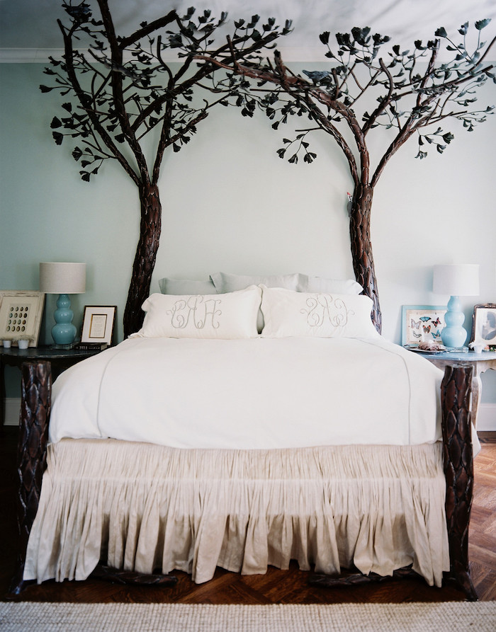 dark brown fake trees, with dark green leaves, wall art décor, placed on witer side of a bed, with white and pale beige covers and pillows