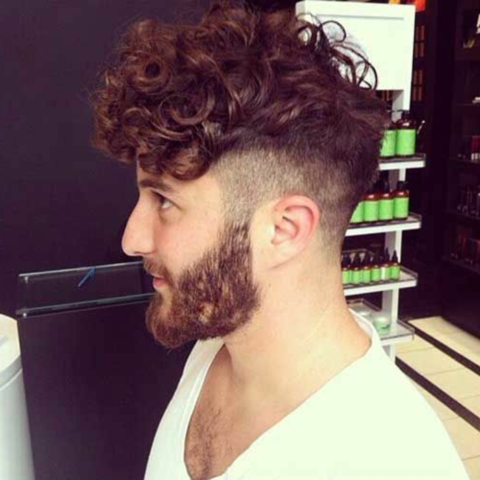 auburn hair on young bearded man, sitting in profile, hairstyles for curly hair, faded undercut long on top, white t-shirt with deep neckline