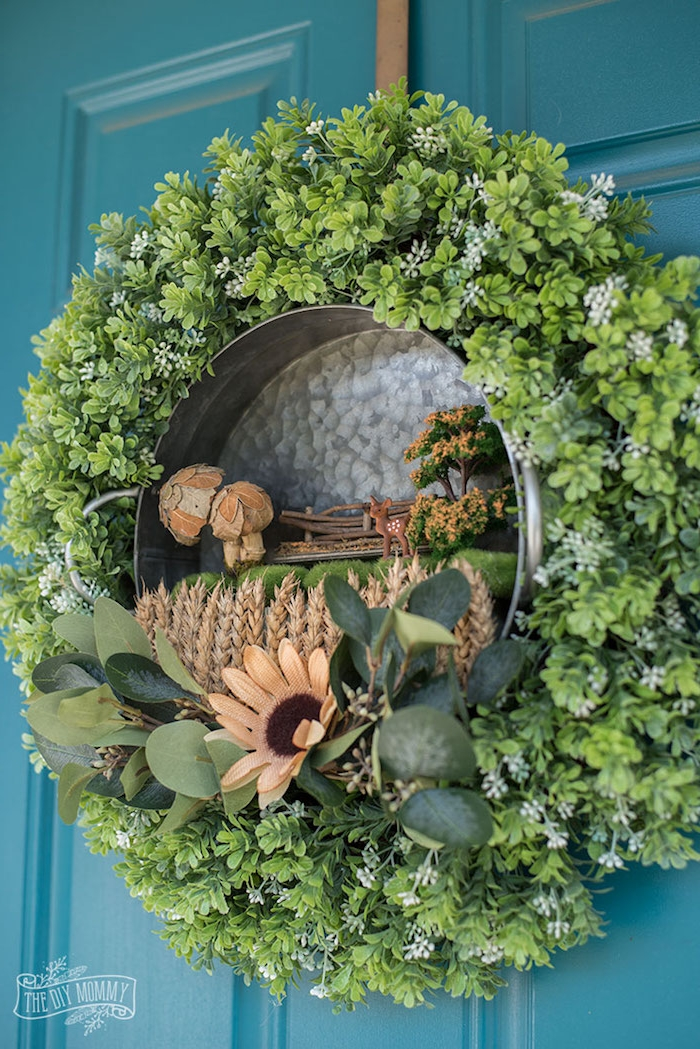 how to make a fairy garden wreath, finished spring decoration, with tiny figurines, moss and dried plants, inside an aluminium cooking pot, decorated with green flowers, and hung on a door