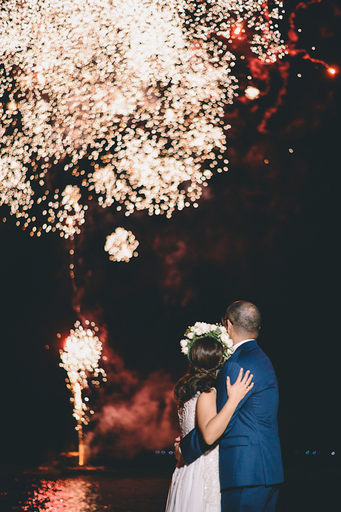 hugging bride in embroidered gown and groom in blue suit, watching fireworks over the sea, in the night sky, beach wedding venues