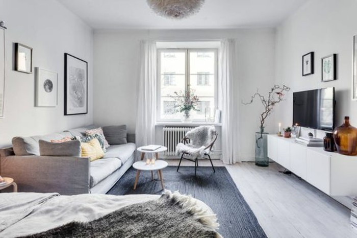 nordic-style studio, white and pale gray walls, light gray sofa and dark gray rug, stylish apartment design, knitted fabrics and fur