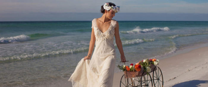 cart with red, white and yellow flowers, pulled by brunette woman, wearing white vintage style, embroidered bridal gown, and a flower crown, beach weddings in florida, sea waves in the background