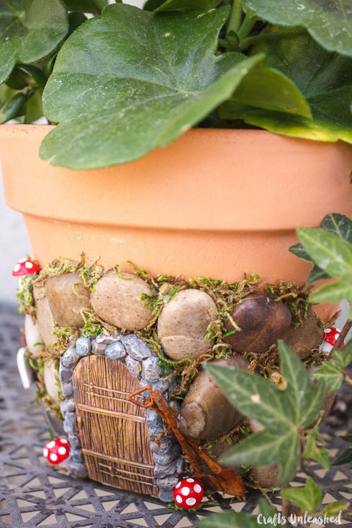 close up of the completed decorated planting pot, fairy garden ideas, ivy and other green plants inside, pebbles and other decorations