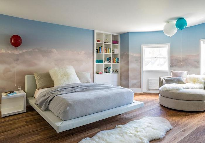 three balloons inside a bedroom, with walls covered in wallpaper or mural, depicting light blue sky, with fluffy cream clouds, wall art décor, white and cream furniture