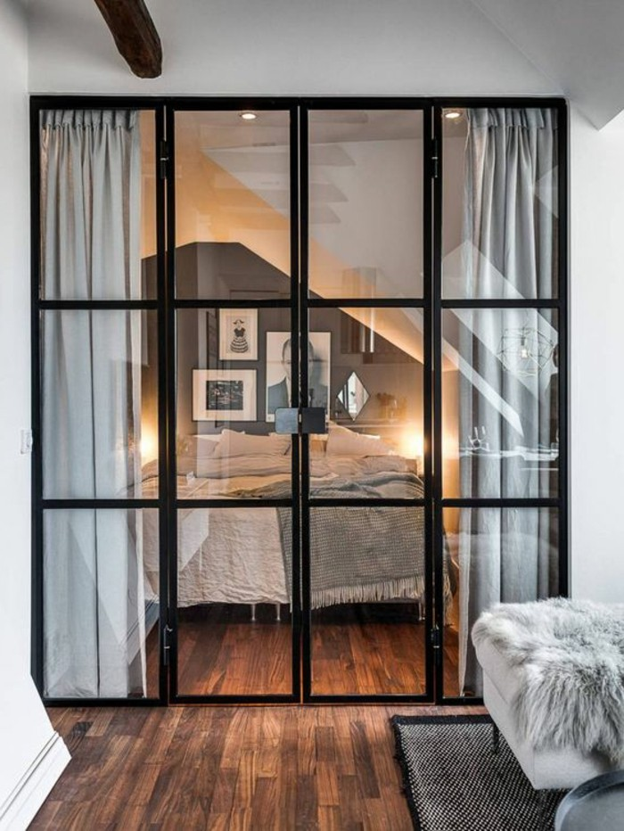 bedroom with dark gray and white walls, and bed with pale gray bed covers, separated from the rest of the studio with folding doors, studio apartment design, brown laminate floor