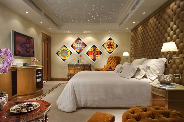 tiny inbuilt ceiling lights, inside a bedroom, with large white fluffy bed, four colorful posters, retro furniture and one soft beige wall