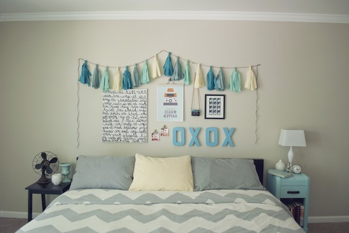 tassels in cream and three shades of blue, attached to a string, hanging over posters and decorations, on wall above a double bed in gray and cream