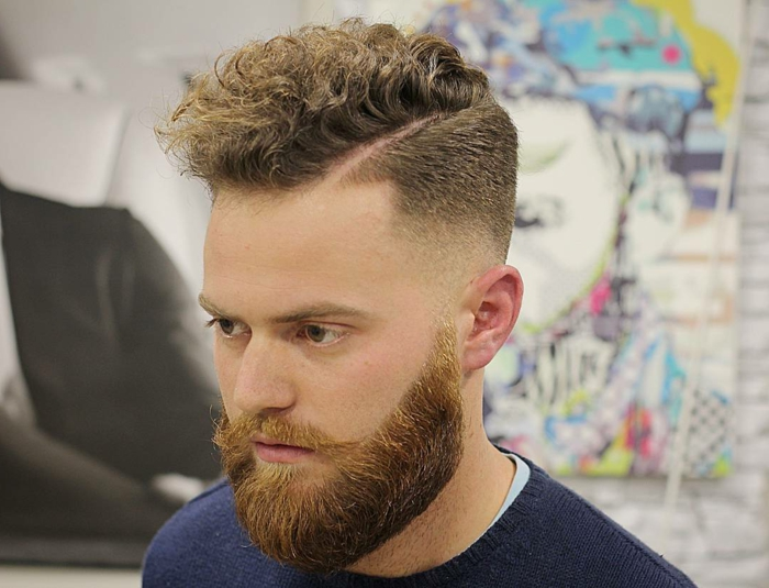 permed quiff on dark blonde hair, worn by man with ginger beard, and a retro mustache, curly haircuts, dark blue jumper