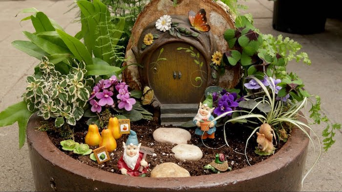 turte and snail, squirrel and gnome, and tiny gourd figurines, decorating a large ceramic pot, containing small burrow-like house ornament, fairy garden pictures, various flowers and plants