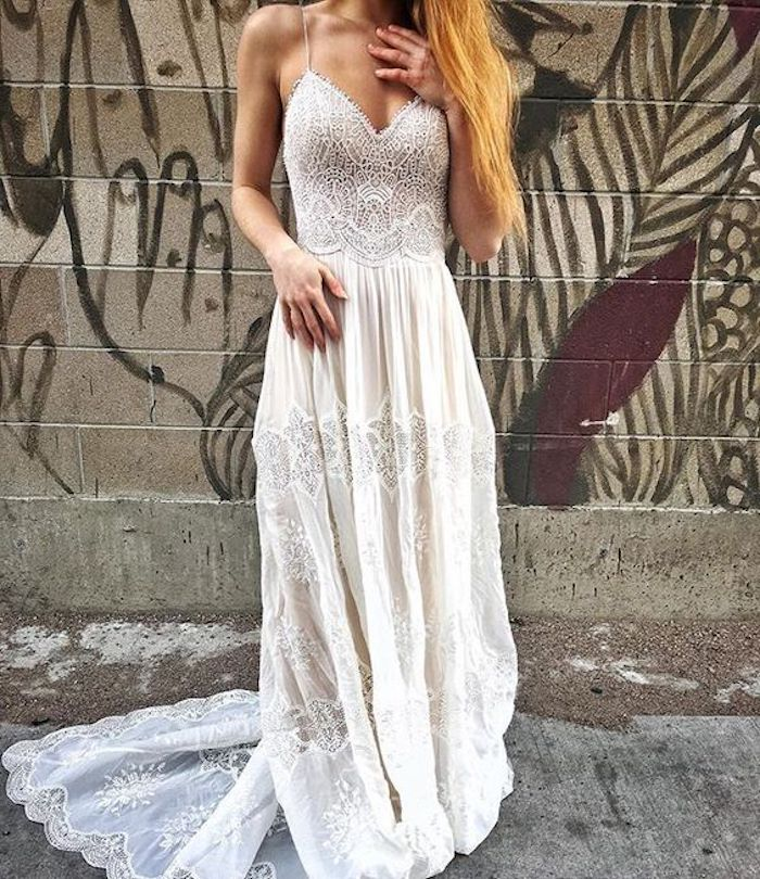 copper blonde woman, dressed in an embroidered, maxi wedding dress, in ivory and white, with long lace hem, standing in front of a graffitied wall