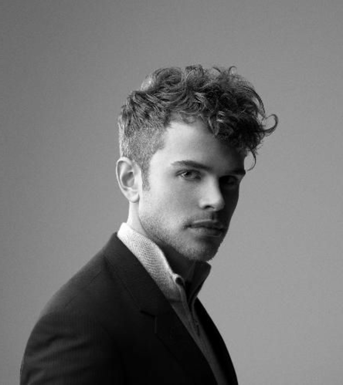 blazer in black, over polo shirt, worn by man with short hair, and longer bangs, curly haircuts, grayscale photo