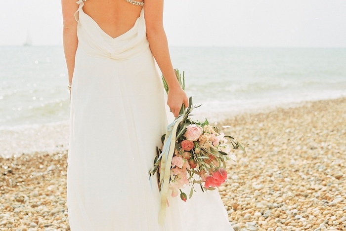 wedding dresses for beach wedding, white grecian style gown, with slouched back, worn by slim woman, standing on a pebbled beach, holding bouquet of pale and saturated pink flowers