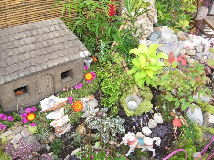 stone house ornament, placed in a garden, with many different flowers and plants, how to make a fairy garden, tiny figurines of a horse and a fairy