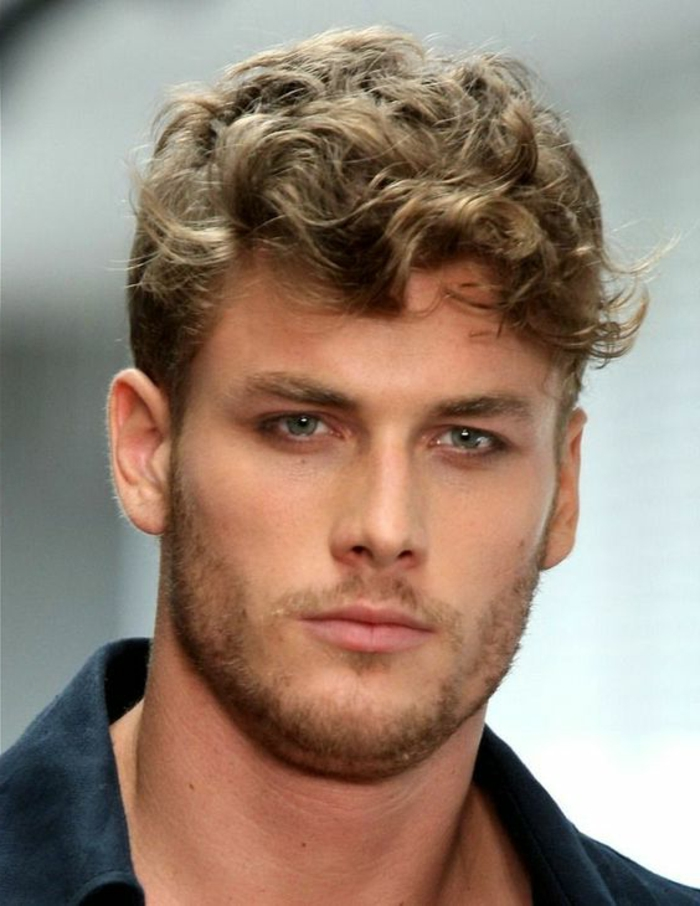 model with stubbly chin and lip, wearing a black shirt, blonde curly hair, styled in a messy look, hairstyles for short curly hair