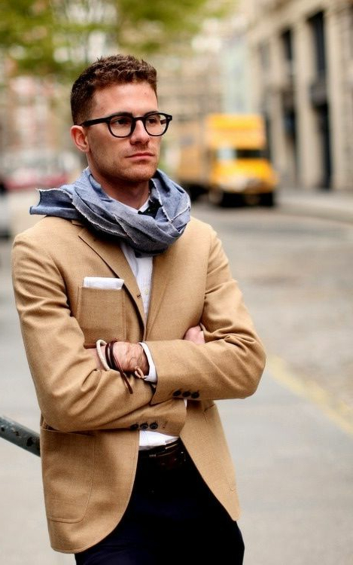 camel colored blazer, worn over white shirt, and black pants, by man with short brunette hair, hairstyles for curly hair, glasses and a light blue scarf