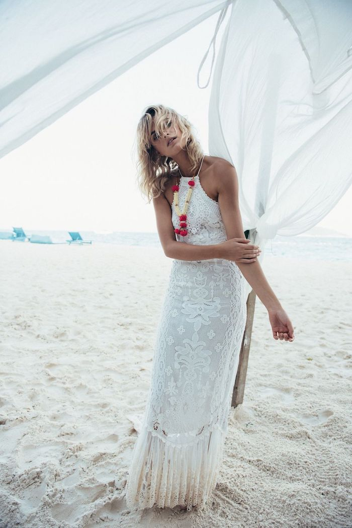 beach with fine white sand, woman with short wet blonde hair, wearing white embroidered halter neck gown, lace details and chunky fabric necklace, beach wedding dresses