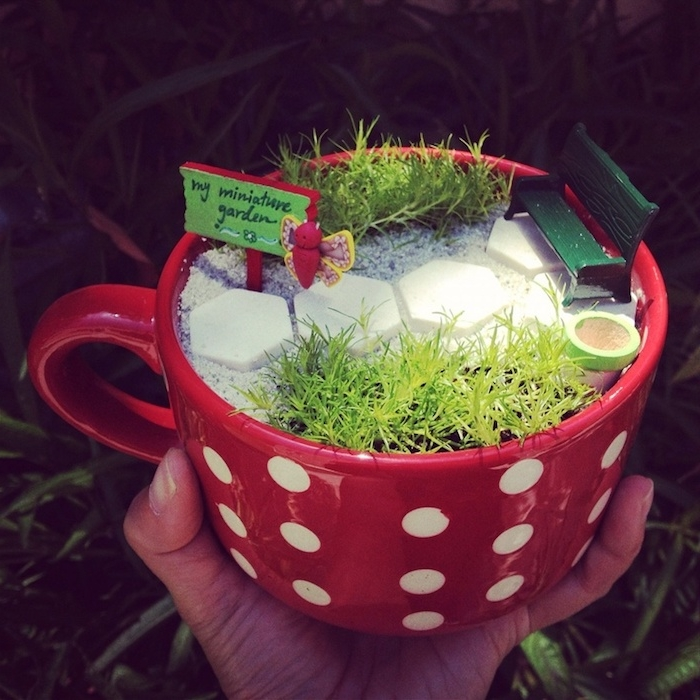 fairy garden images, large mug in red, with white polka dots, filled with fine sand, decorated with tiny dark green bench, small sign reading my miniature garden, green grass and others