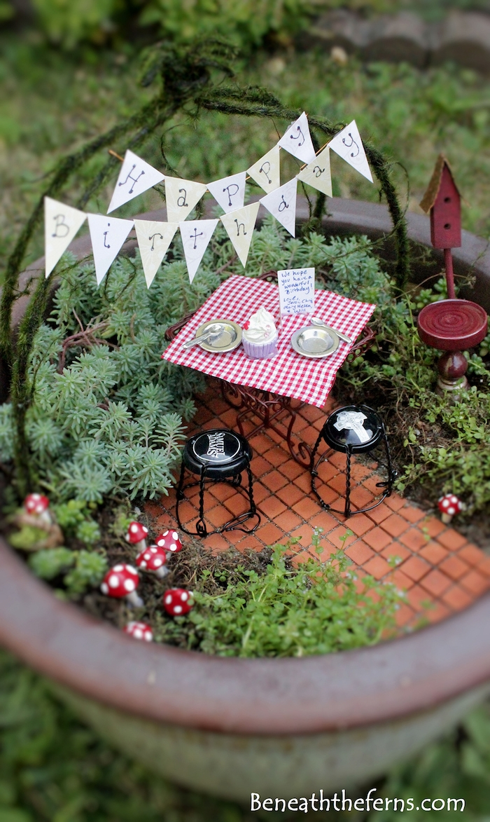 banner with the words happy birthday, inside a miniature fairy garden, with a tiny table, and chairs made from champagne caps, tiny cake and plates, various green plants