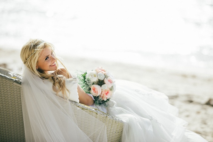 long sheer white veil, worn by smiling blonde bride, sitting on an ivory-colored wicker settee, placed on a sandy beach, wedding dresses for beach wedding, bouquet of white and pale peach flowers