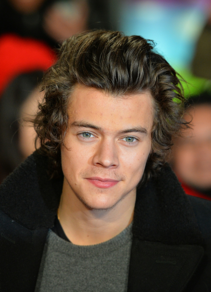 former one direction member, harry styles with wavy, messy brunette hair, bangs slicked back, curly hairstyles, wearing gray jumper, and black woollen coat with large collar