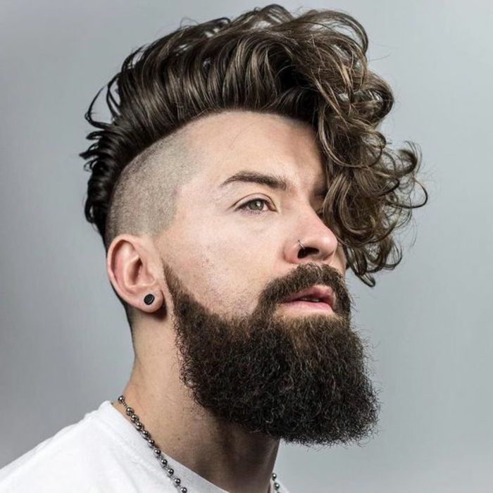 long beard with mustache, worn by hipster style man, with deep curly undercut, brushed to one side, hairstyles for curly hair, nose ring and black earring