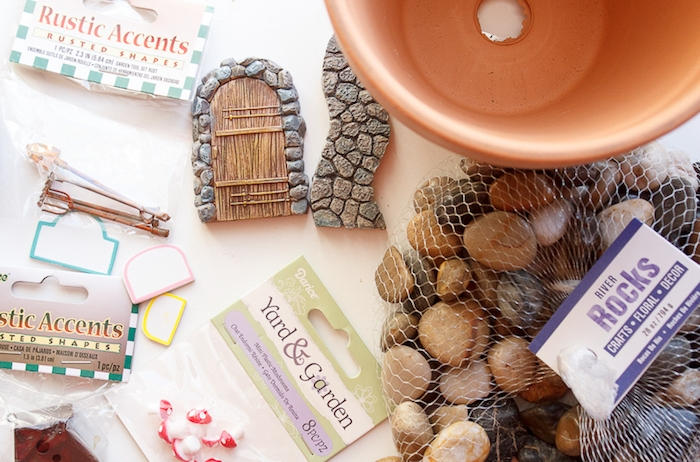 materials needed for making a fairy house planting pot, pebbles in a net bag, empty ceramic pot, fairy garden ideas, stickers and little clay ornaments