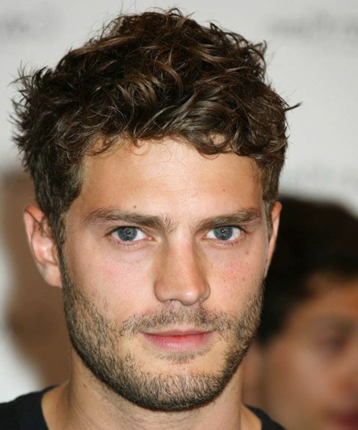 messy short curly hair, worn by jamie dornan, with short beard and mustache, blue eyes and a smile, wearing black t-shirt
