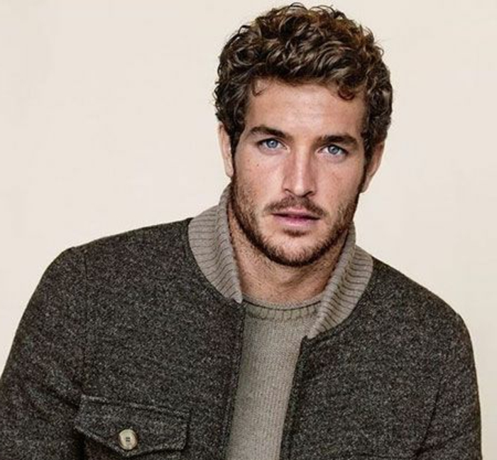 dynamic curly hairstyle, on a brunette man with blue eyes, wearing dark gray jacket, over khaki grey knitted jumper