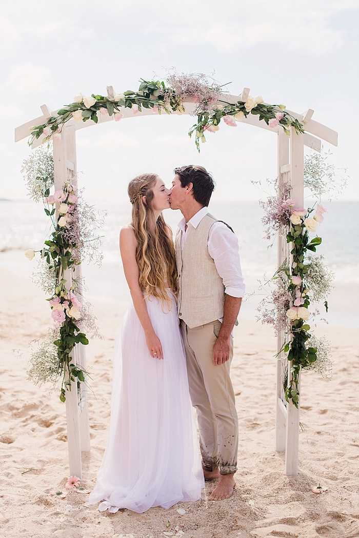 young woman with wavy highlighted dark blonde hair, wearing a white maxi dress with tulle skirt, kissing a man in pale beige suit, under a wedding arch, beach wedding venues near the sea