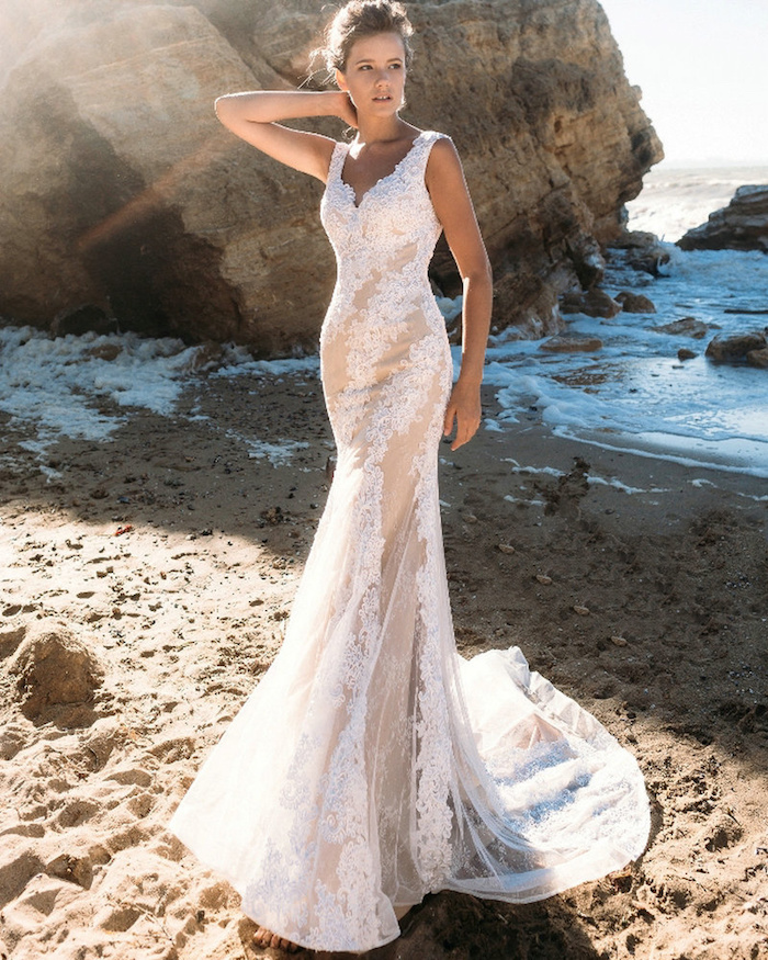 classical mermaid lace beach wedding dress, in white and cream, worn by tall and slim young woman, with brunette hair in a messy hairdo, boulders sand and sea