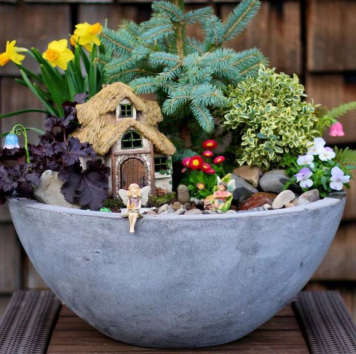 fir branch and many different flowers, and green plants, inside a large gray bowl, with pebbles and fairy figurines, pansies and daffodils