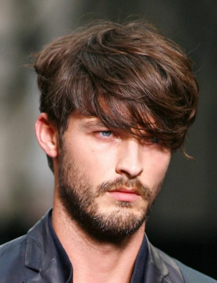 bangs falling over one eye, brunette textured and layered haircut, worn by blue-eyed man, with short beard and mustache