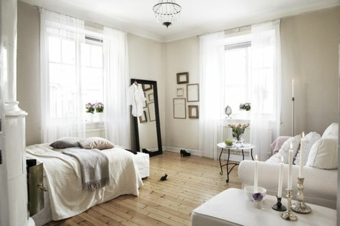 mirror in black frame, leaning against a pale beige wall, inside a room with two windows, sofa and bed, how to decorate a studio apartment