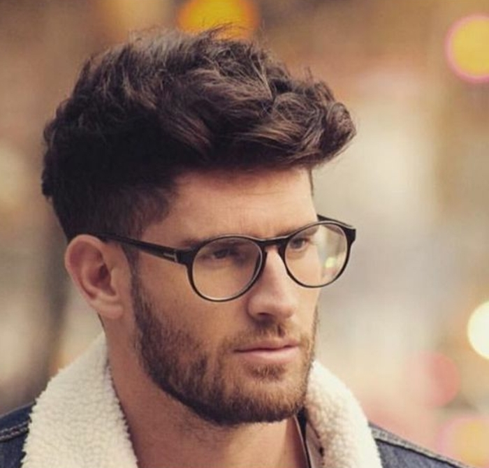 curly hairstyles, brunette hair with short sides, left longer on top, worn by man with beard, mustache and glasses, denim jacket with white fluffy collar