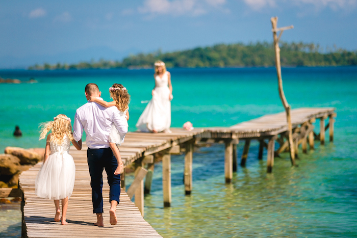 beach wedding venues, tropical sea in azure blue, man and two young girls, walking on a boardwalk, towards a blonde woman, in a long white gown