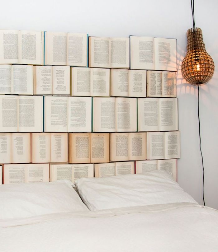 five rows of open books, with white and yellow pages, decorating a white wall, behind a double bed, and near a unique hanging lamp, wall decor ideas