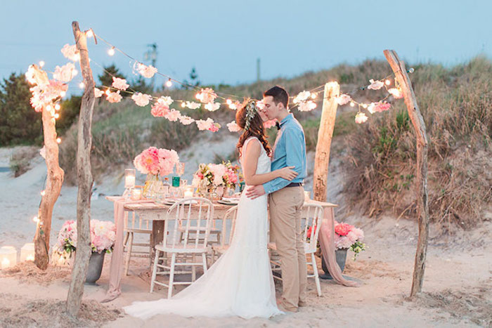pink flowers in different tones, in bouquets and garlands, on and near a set white rustic table, with matching chairs, florida destination weddings, young couple kissing