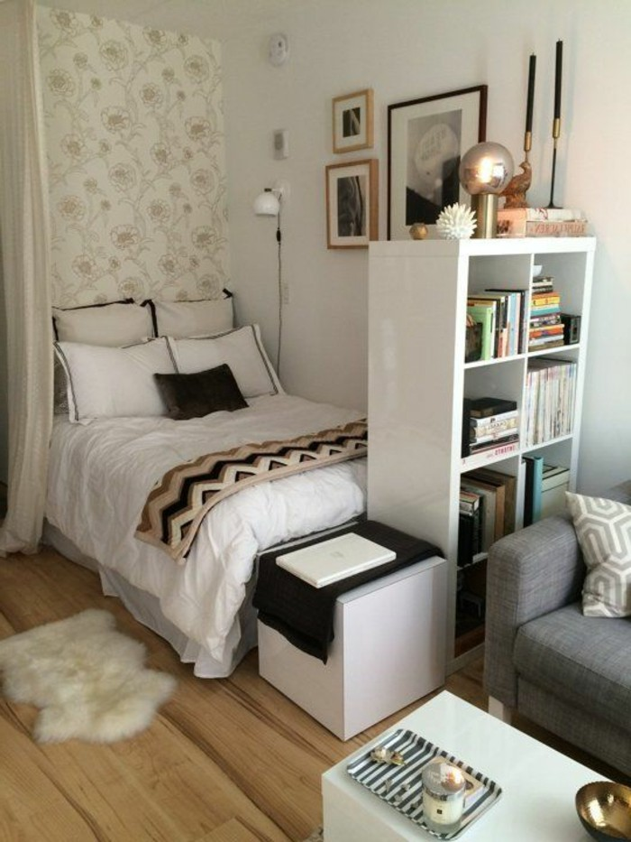 floral wallpaper in pale beige and white, near bed with four sets of pillows, wooden floor and sheepskin rug, studio apartment decorating ideas, gray sofa and white coffee table nearby