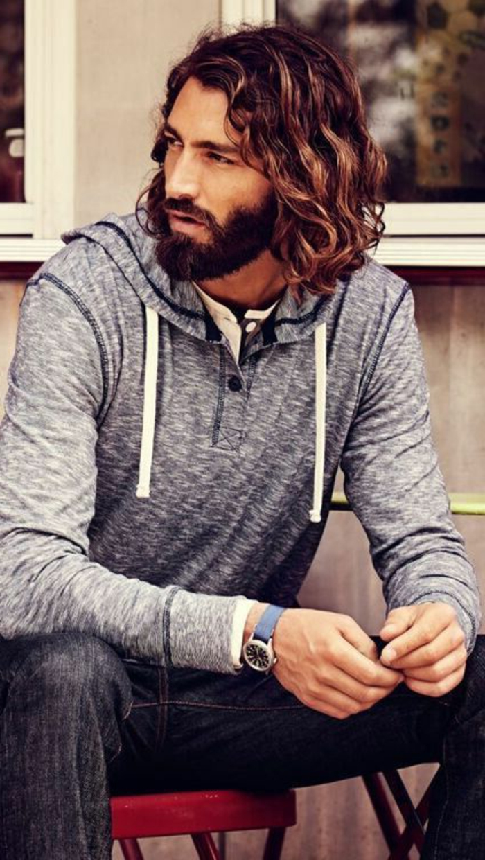 grey hoodie and dark gray jeans, worn by bearded man, with mustache and medium length wavy brunette hair, haircuts for men with curly hair, dark blonde highlights