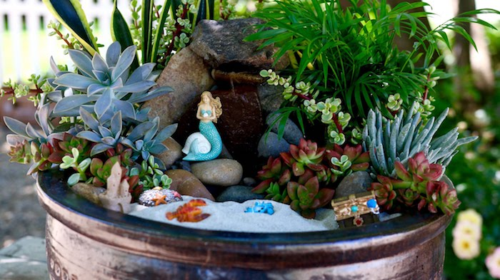 sea-side inspired succulent fairy garden, with fine gray sand, and tiny figurines, treasure chest and grabs, sand castle and mermaid