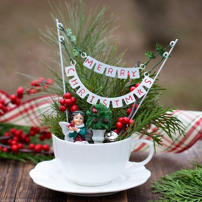 white porcelain teacup, filled with fir branches, holly berries and little christmas figurines, with a white banner, reading happy christmas, matching white saucer