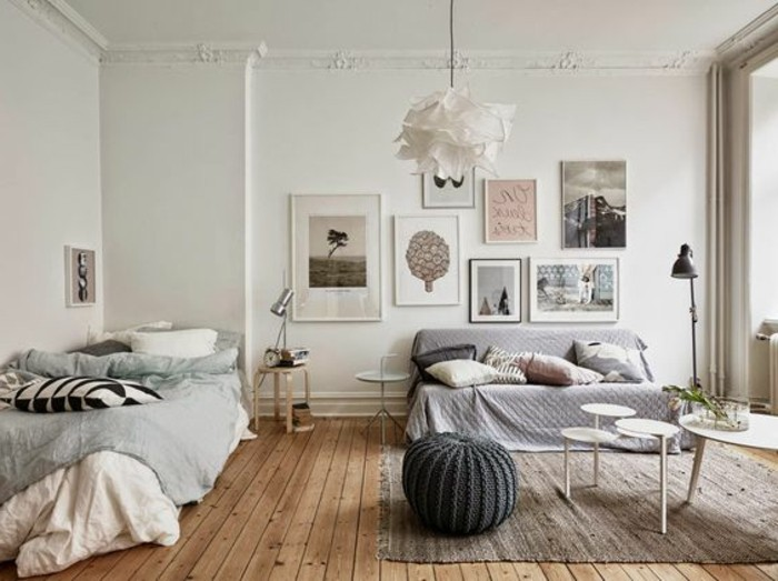 color scheme in soft pastel tones, inside room with white walls, decorated with several framed images and posters, small apartment living room ideas, sofa with several cushions, light brown rug